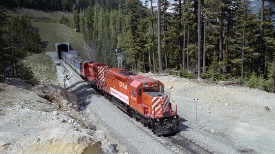 Photo en couleur d'un train avec locomotive rouge qui émerge d'un tunnel de base, en été.
